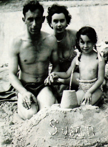 With her name spelled out on the sandcastle the writer, then agreed five, enjoys a holiday with her parents on Hamworthy Beach in 1952.