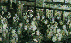 Now who hasn't got their arms crossed? Little Ann Priest (ringed), sits at the back of the tiled classroom in 1945 where, typically, children were seated in pairs at solid wooden desks mounted on iron frames.