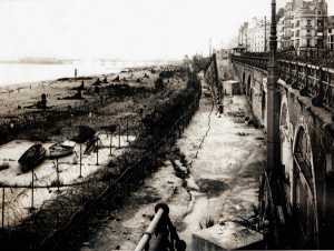 A fortified Brighton sea front during the Second World War, with barbed wire on both upper and lower esplanades, rows of beach defences and a pier deliberately cut in half.
