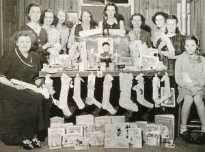 Stockings made and filled by Camp Fire Girls and their leaders ready to be delivered to a children's home, along with a variety of toys and books donated by the girls in preparation for Christmas in the early 1950s.