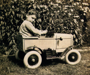 As a child in the 1930s Peter Pitt is photographed in his toy car - and what a car it was - right down to the motor spirit can on the footboard!