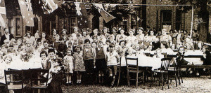 Partying on VE Day 1945, showing the horse chestnut trees and grassed area, with the author in a jester's suit at the extreme right end of the table.